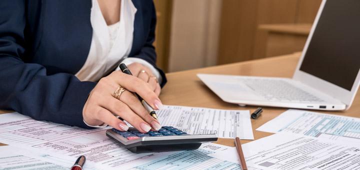 mujer calculadora documentos laptop oficina