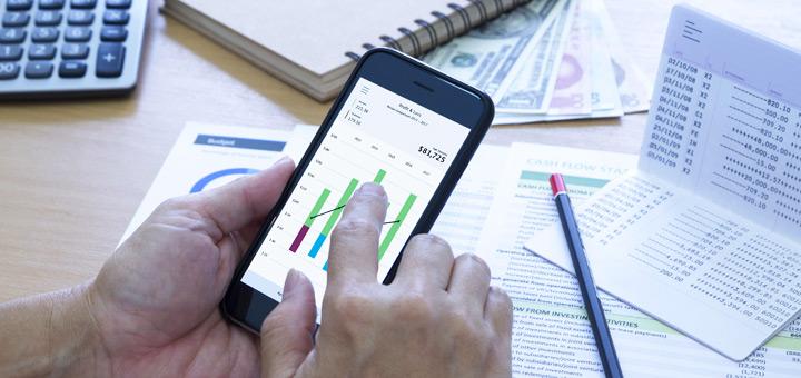 manos celular gráficos finanzas